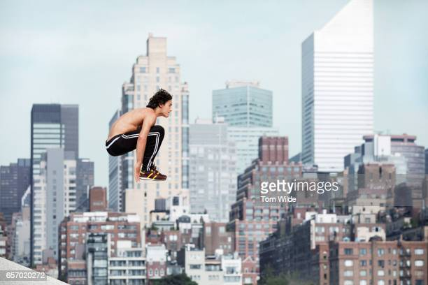 Caucasian male free running and jumping with the manhattan skyline in the background