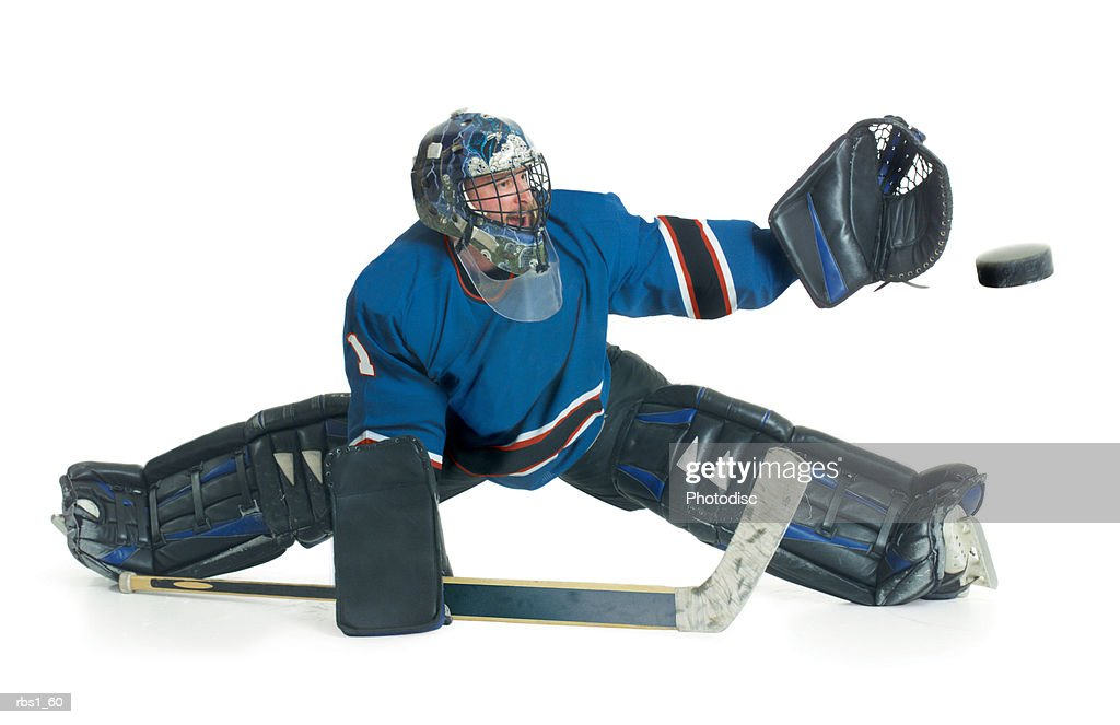 A caucasian male hockey goalie in a blue uniform splits his legs and reaches for the puck to block a shot : Foto de stock