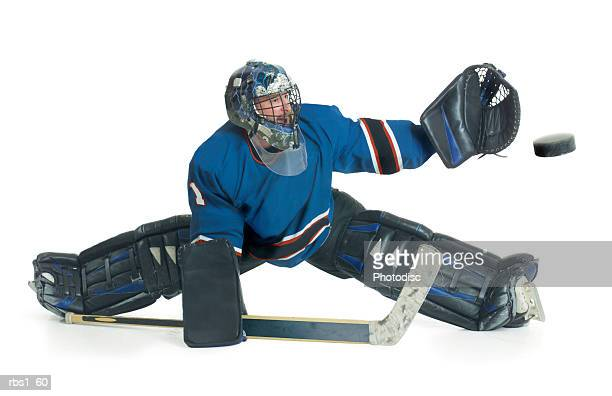 a caucasian male hockey goalie in a blue uniform splits his legs and reaches for the puck to block a shot - hockey player stock pictures, royalty-free photos & images
