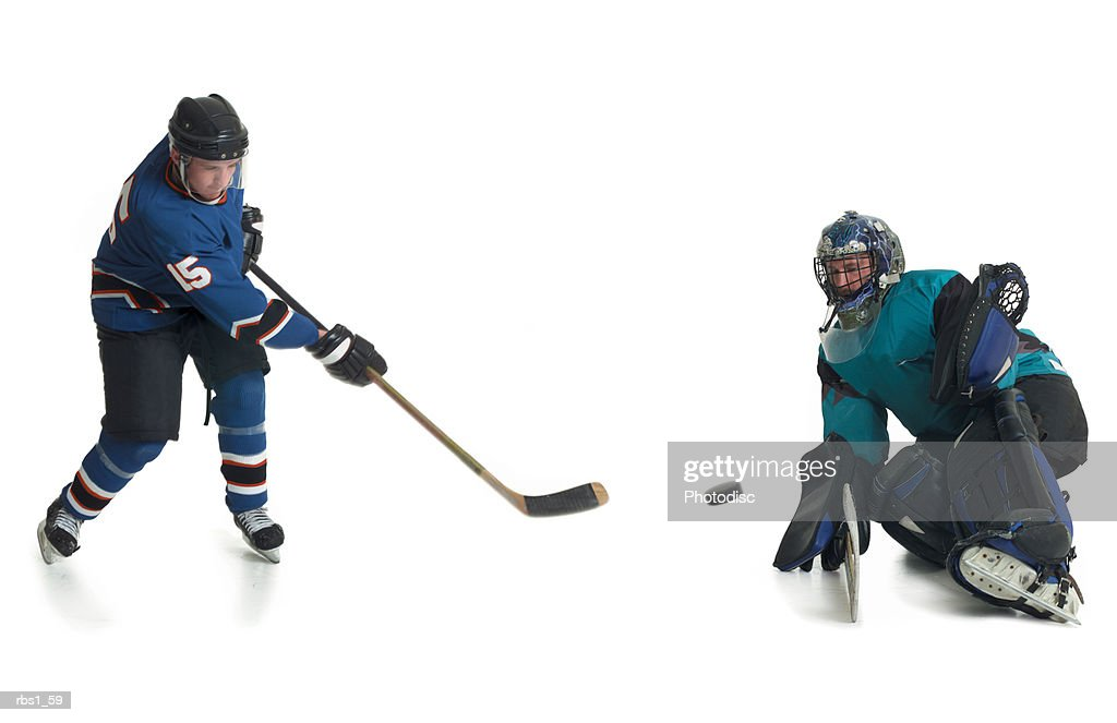 A caucasian male hockey player in a blue jersey skates and shoots his puck towards the goalkeepeer of the opposing team : Foto de stock