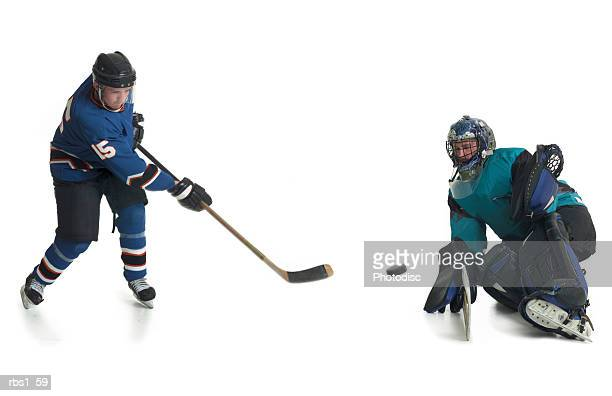 a caucasian male hockey player in a blue jersey skates and shoots his puck towards the goalkeepeer of the opposing team - ice hockey player stock pictures, royalty-free photos & images
