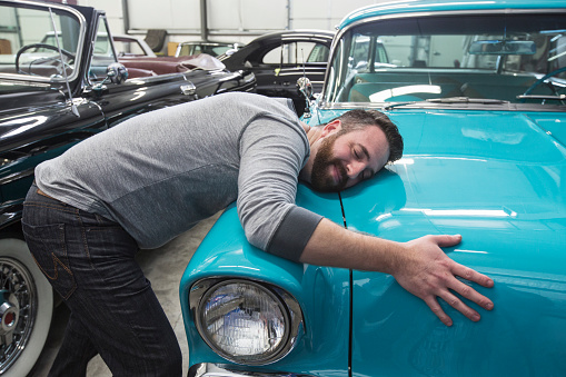 A Caucasian male hugging the hood of his old sedan in a classic car repair shop. - gettyimageskorea