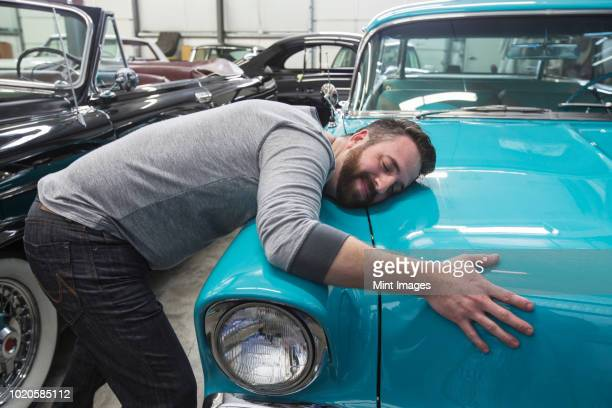 a caucasian male hugging the hood of his old sedan in a classic car repair shop. - amor imagens e fotografias de stock