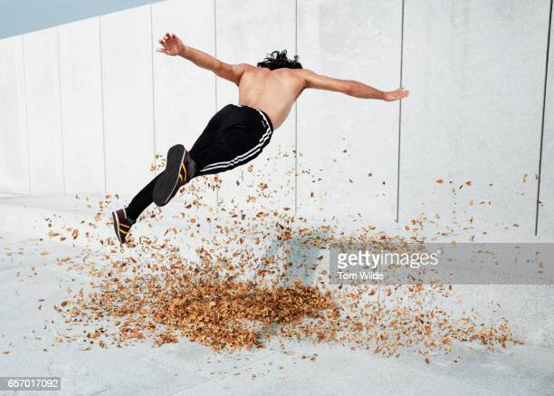 Caucasian male jumping over a pile of autumn leaves in an urban environment.