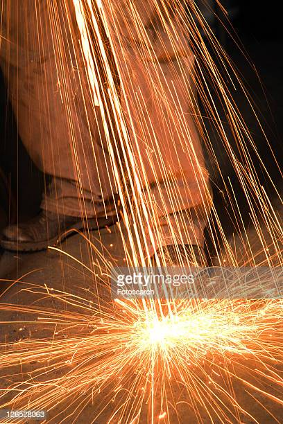 Caucasian male metalsmith shaping metal and creating sparks.