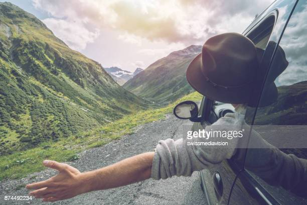 caucasian male on road trip enjoying mountain landscape - escapism stock photos and pictures