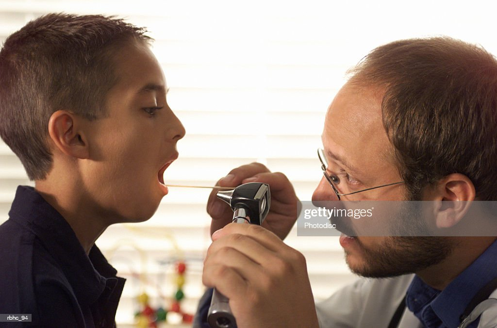caucasian male pediatrician with beard examines the throat of a young boy patient during a check up : Stockfoto