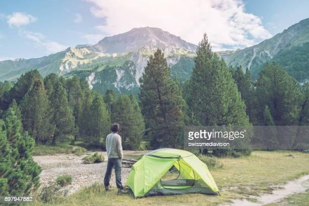 Mâle caucasien reposant à côté de la tente au coucher du soleil, Suisse