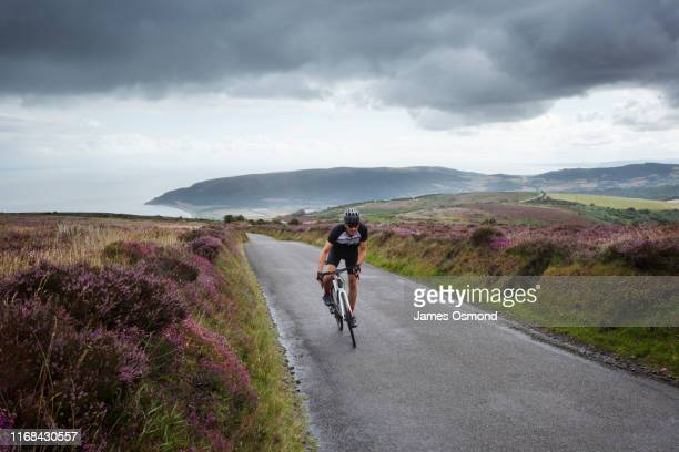 caucasian male road cyclist climbing uphill on country road crossing moorland. - road stock pictures, royalty-free photos & images