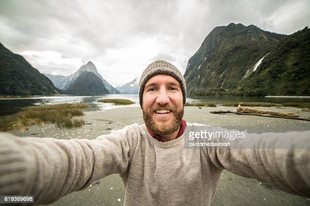 Caucasian male traveling takes selfie portrait with mountain landscape