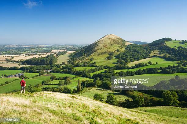 caucasian male walker (30 years old) on caer caradoc hill looking towars the lawley. shropshire. england. uk. - hill stock pictures, royalty-free photos & images