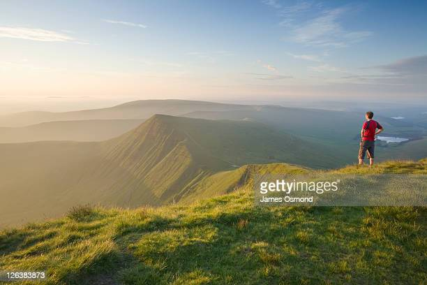 Caucasian Male Walker (30 years old) on Pen y Fan summit at sunrise looking towards Cribyn, Brecon Beacons National Park, Powys, Wales UK