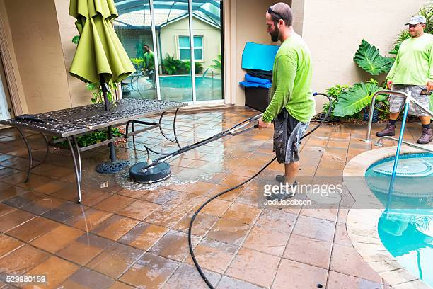 Caucasian male worker power washing residential pool patio tiles