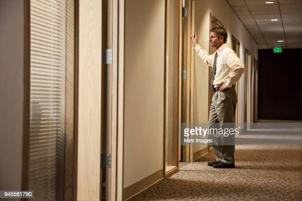 caucasian man a hallway meeting with another person in an office. - one man only stock pictures, royalty-free photos & images