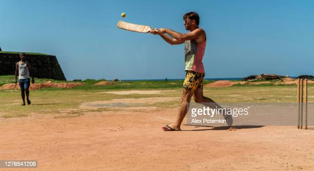 caucasian man, a tourist, learning how to play cricket in sri lanka with the local team. he are playing the batsmen who are defending the base - hitting the ball with a bat. - cricket bat stock pictures, royalty-free photos & images