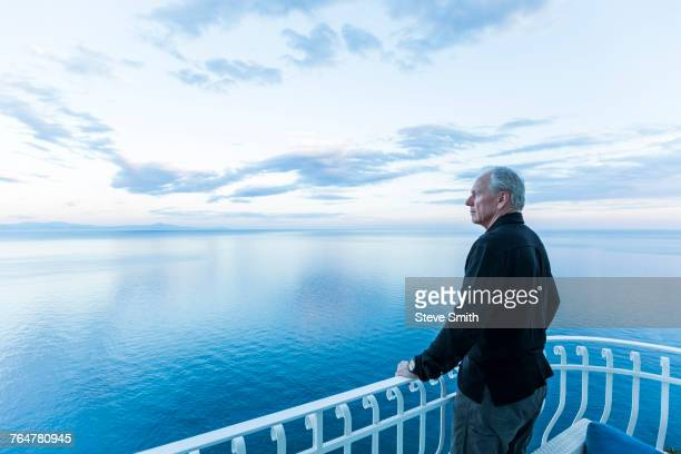 Caucasian man admiring scenic view on waterfront balcony