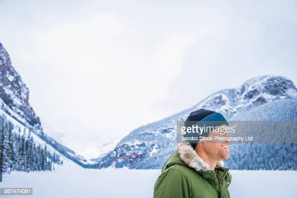 caucasian man admiring snowy mountains, lake louise, alberta, canada - フード付きコート ストックフォトと画像