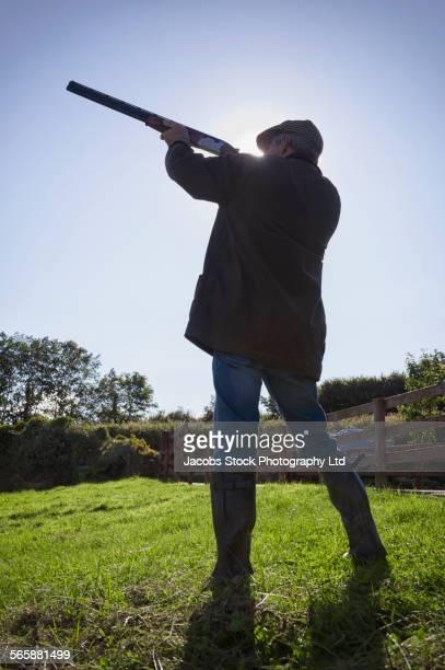 Caucasian man aiming shotgun in rural field