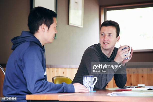 Caucasian man and Asian(Japanese) man having a coffee break and talking in the room