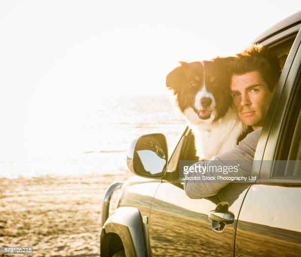 Caucasian man and dog in car window on beach