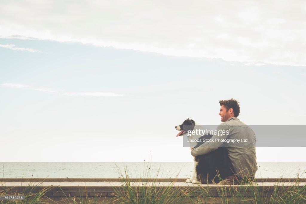 Caucasian man and dog sitting on boardwalk : Stock Photo