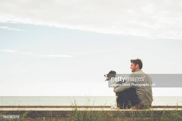 Caucasian man and dog sitting on boardwalk