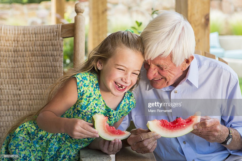 Caucasian man and granddaughter eating watermelon : Stock Photo