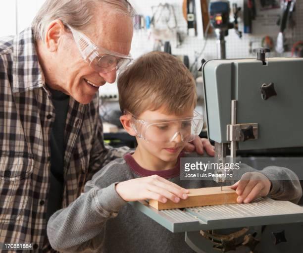 caucasian man and grandson working in woodshop - 電動糸のこ ストックフォトと画像