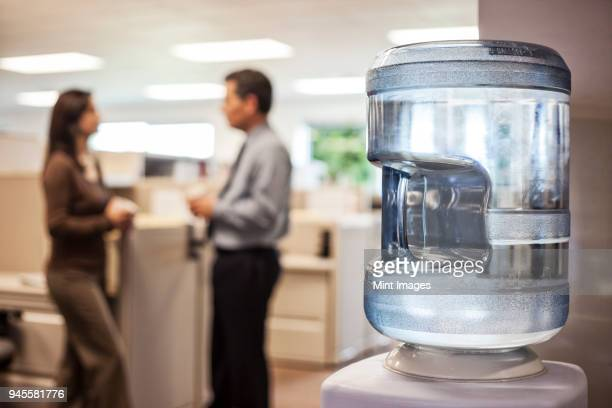 caucasian man and woman executives in cubicle area of new office space - water cooler stock photos and pictures