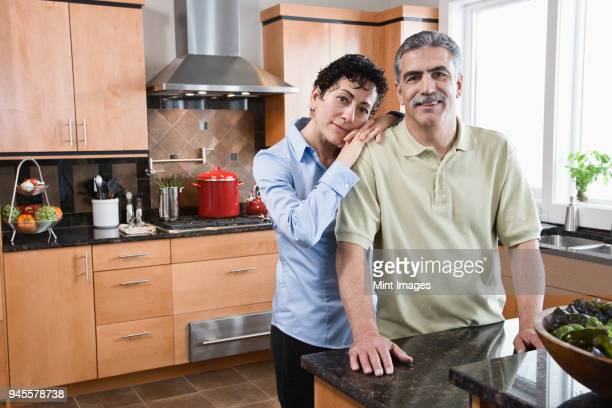 caucasian man and woman preparing a meal in their new kitchen. - early retirement stock pictures, royalty-free photos & images