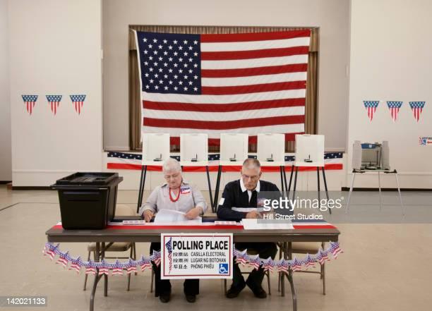 caucasian man and woman working at polling place - voter registration photos et images de collection