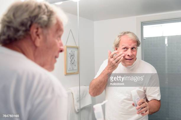 Caucasian man applying lotion to face in mirror