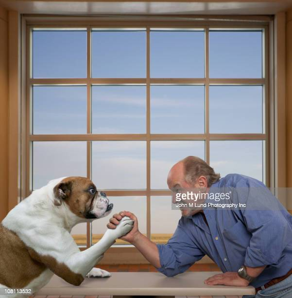 Caucasian man arm wrestling with dog