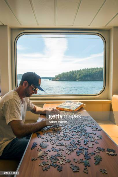 caucasian man assembling jigsaw puzzle in boat near window - houseboat stock pictures, royalty-free photos & images