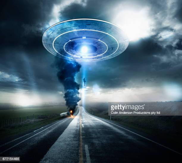 caucasian man beaming up to ufo over highway - ovni fotografías e imágenes de stock