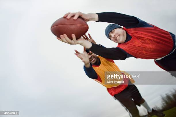 Caucasian man being tackled by an opponent, and diving with arms outstretched to score, holding a football. An non-contact flag football match. View from below.