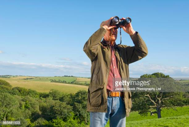 Caucasian man bird watching with binoculars in rural field