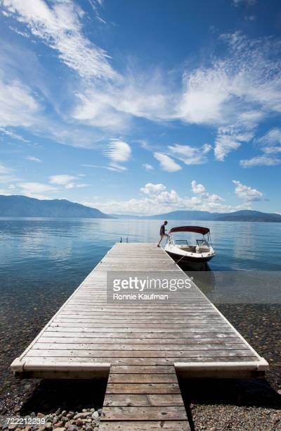 Caucasian man boarding boat in river from wooden dock