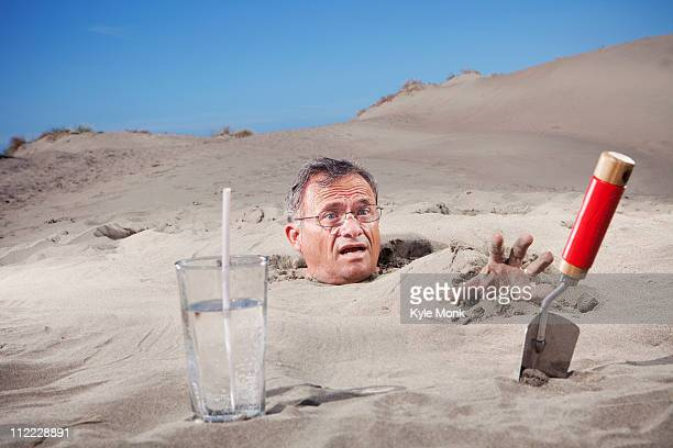 Caucasian man buried in sand next to glass of water and trowel