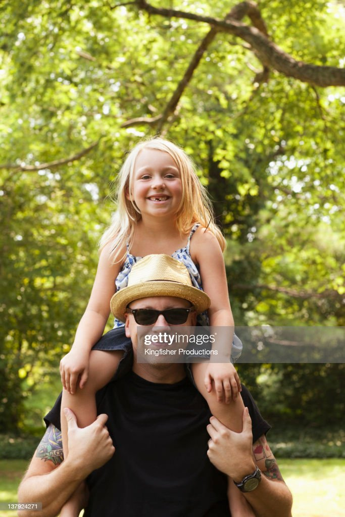 Caucasian man carrying daughter on shoulders : Stock Photo