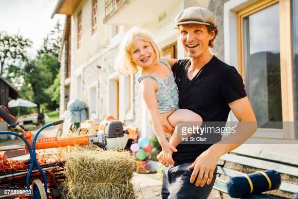 Caucasian man carrying daughter