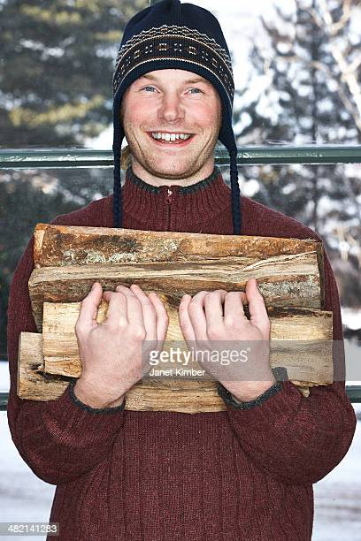Caucasian man carrying firewood in snow