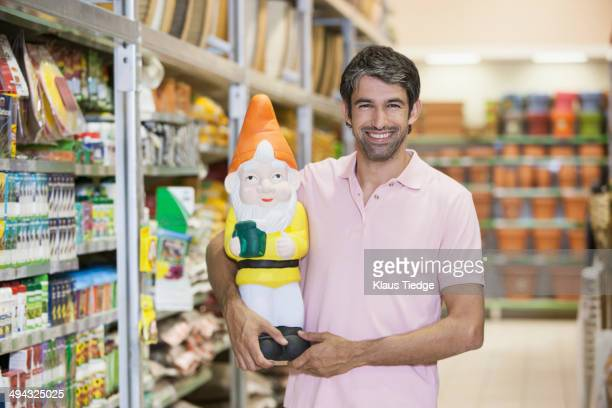 Caucasian man carrying garden gnome in hardware store