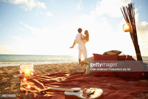 caucasian man carrying girlfriend on beach - honeymoon stock photos and pictures