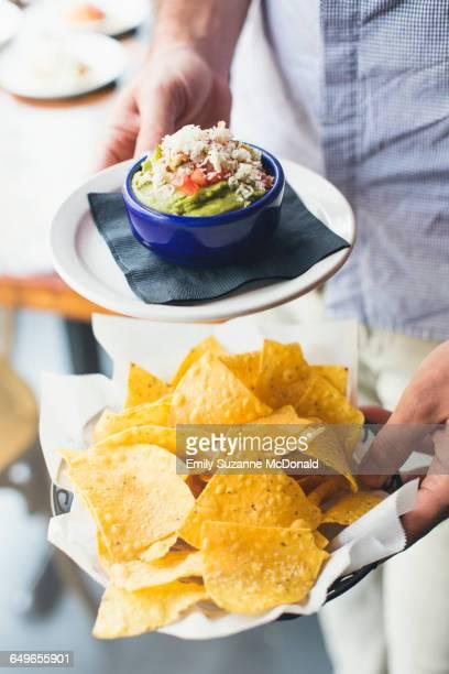 Caucasian man carrying guacamole and tortilla chips