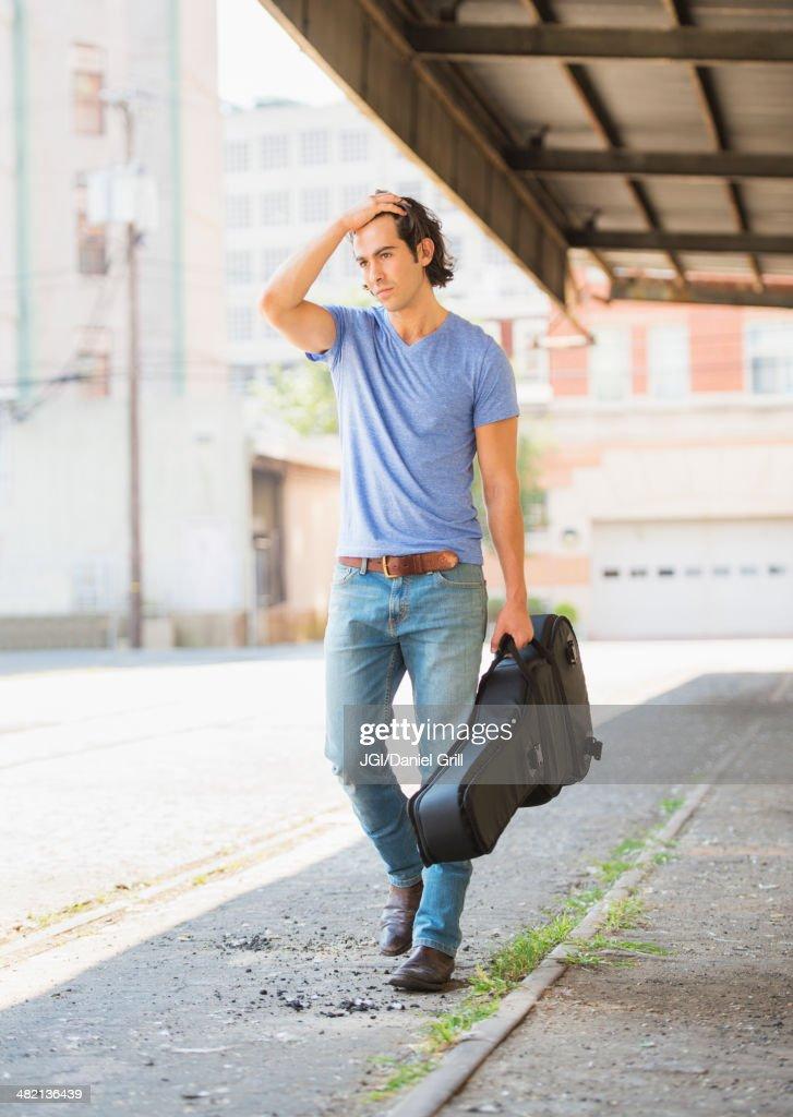 Man With Guitar Walking On Sidewalk Stock Photo