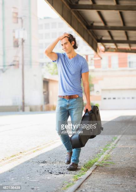 caucasian man carrying guitar case on city street - guitar case stock pictures, royalty-free photos & images