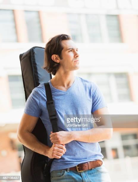 Caucasian man carrying guitar case on urban street