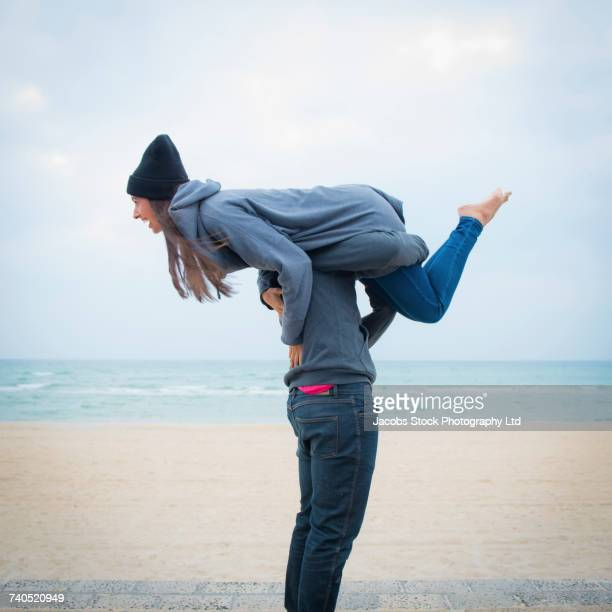 Caucasian man carrying laughing woman on shoulder on beach