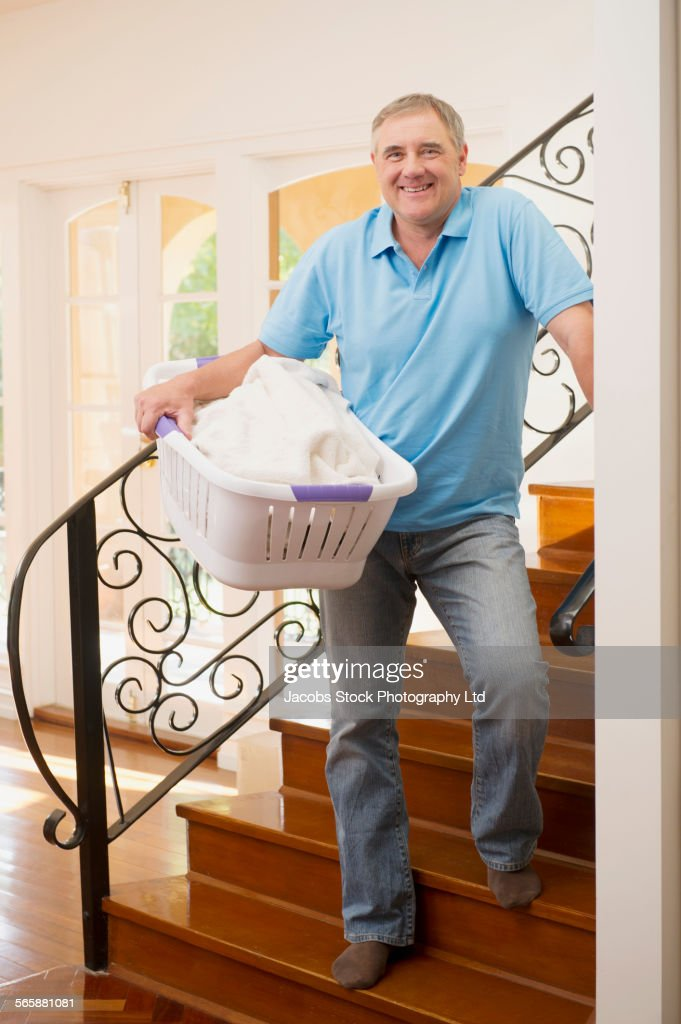Caucasian Man Carrying Laundry Basket On Staircase